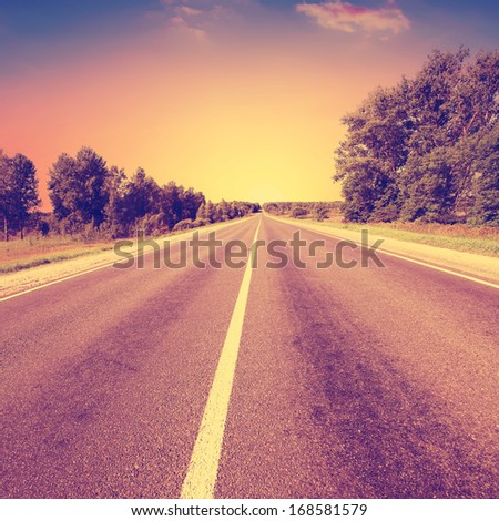 Vintage photo of country asphalt road. - stock photo