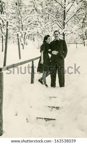 Vintage photo of couple walking in winter, fifties - stock photo