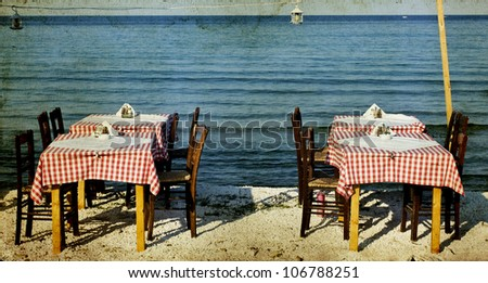 Vintage photo of dining table and chairs set outside on a beach