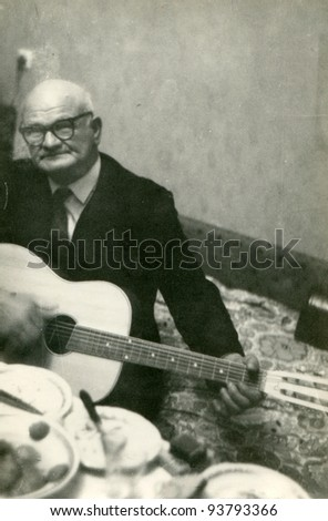 Vintage photo of elderly man playing guitar (seventies) - stock photo
