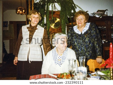 Vintage photo of elderly woman and her adult daughters during a Christmas dinner, eighties - stock photo