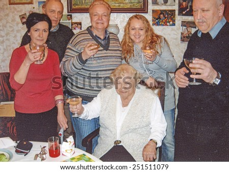 Vintage photo of elderly woman  raising her glass with her family, nineties - stock photo