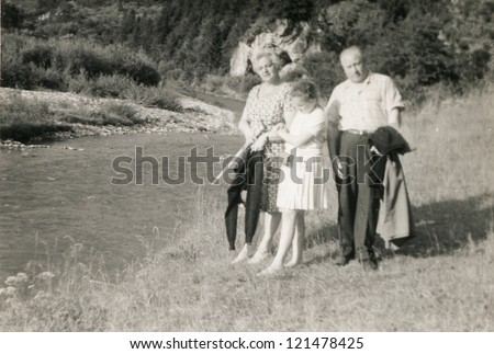 Vintage photo of family (grand father, mother and daughter) walking at riverside (sixties) - stock photo