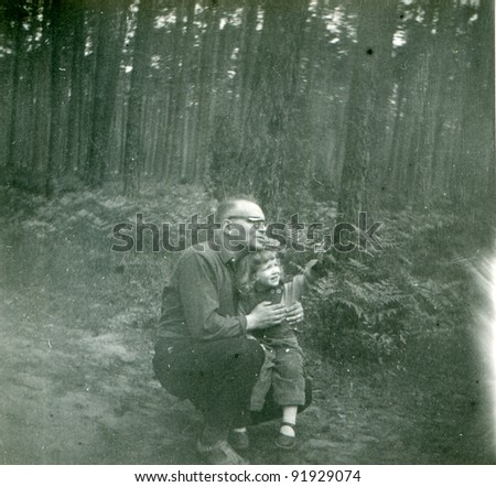 Vintage photo of father and daughter in forest (fifties) - stock photo