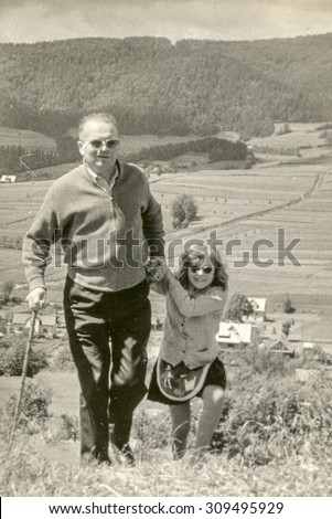 Vintage photo of father and daughter walking in mountains, 1950's