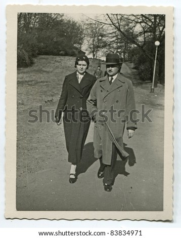 Vintage photo of father and daughter walking on the street (1936) - stock photo