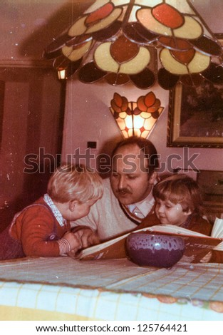 Vintage photo of father reading to his children (eighties) - stock photo