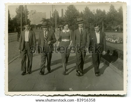 Vintage photo of  father, uncle, sons and daughter walking on the street (thirties) - stock photo