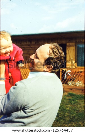 Vintage photo of father with a baby girl (early eighties) - stock photo