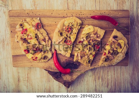 Vintage photo of focaccia with olives, peppers and chicken - stock photo