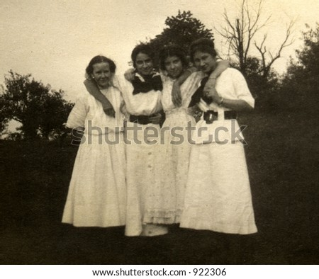 vintage photo of four young women. Circa 1910 print has scratches, fading, solarization, and soft qualities. - stock photo