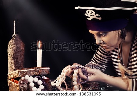 Vintage photo of girl the pirate with greed looking at jewelry - stock photo
