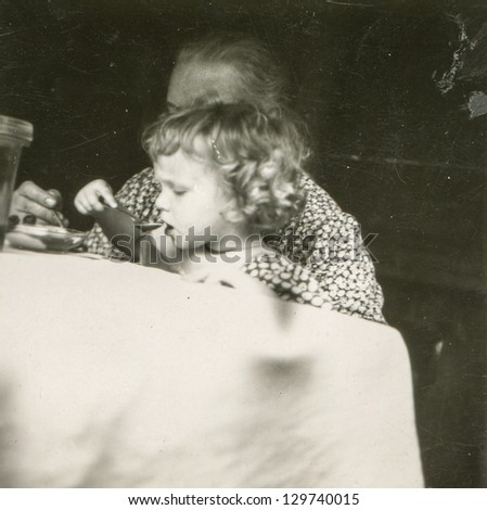 Vintage photo of grandmother feeding her granddaughter, fifties - stock photo