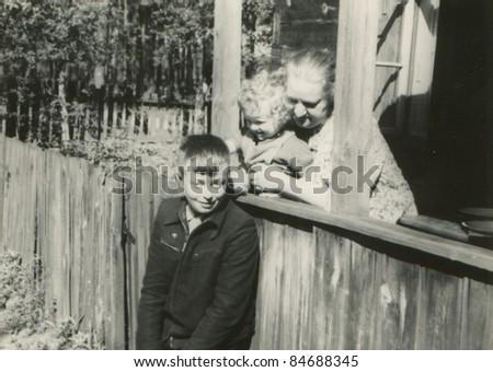 Vintage photo of grandmother with grandchildren (fifties) - stock photo