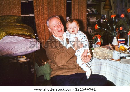 Vintage photo of great grandfather with his baby great granddaughter (early seventies) - stock photo