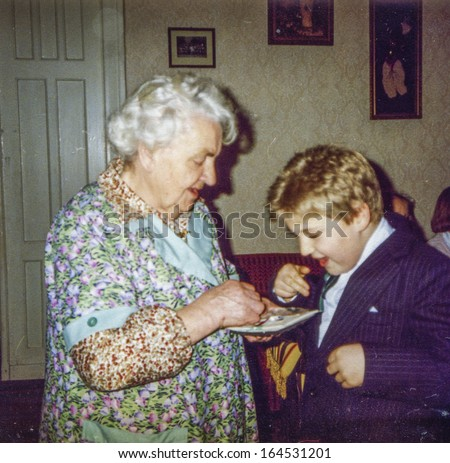 Vintage photo of great-grandmother and great-grandson blessing each other and sharing Christmas wafer during Christmas Eve Vigil, eighties - stock photo