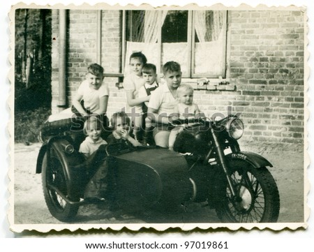 Vintage photo of group of children on motorcycle with a trailer (fifties) - stock photo