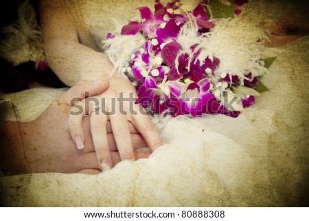 Vintage photo of hands and rings on wedding bouquet - stock photo