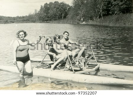 Vintage photo of happy family on pedalo (sixties) - stock photo