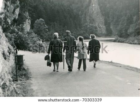 Vintage photo of happy three generations family walking - stock photo