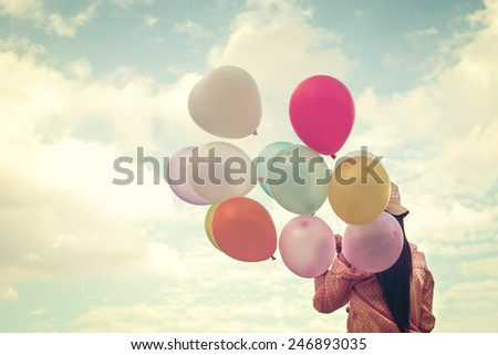 Vintage photo of  Happy young girl  holding colorful balloons and flying on clouds sky background. - stock photo