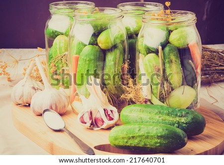 vintage photo of jars of homemade preserves with pickled cucumbers - stock photo