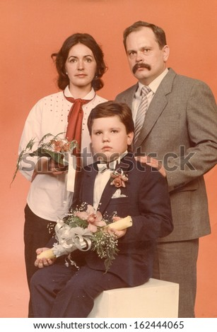 Vintage photo of little boy and his godparents at his First Communion, eighties - stock photo