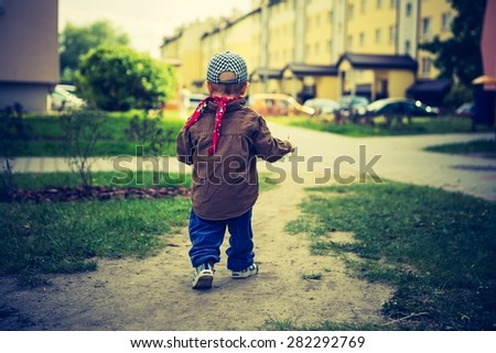 Vintage photo of Little child playing outdoor. photo with old colors effect - stock photo