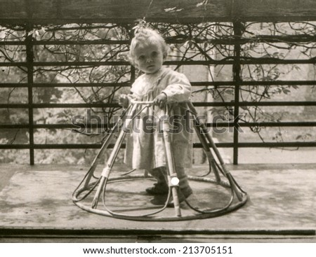 Vintage photo of little girl in a baby walker (fifties) - stock photo