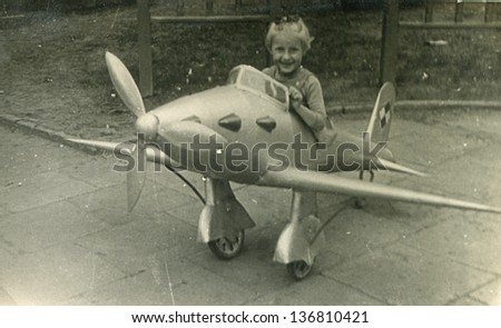 Vintage photo of little girl in toy plane (fifties) - stock photo
