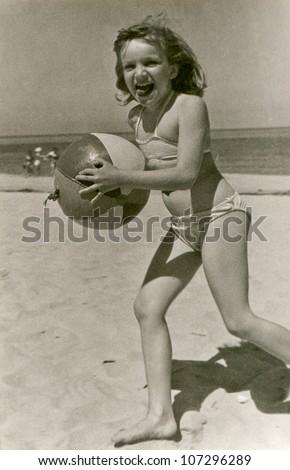 Vintage photo of little girl on beach (fifties) - stock photo