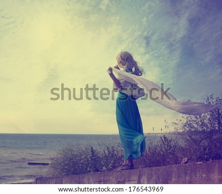 Vintage Photo of Lonely Woman with Waving Scarf at the Sea. Toned Photo with Copy Space. Solitude Concept. - stock photo