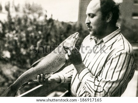Vintage photo of man holding caught fish (1970's) - stock photo