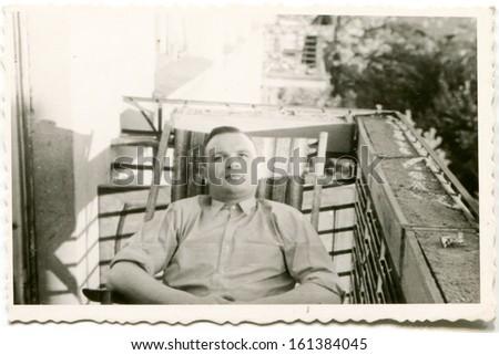 Vintage photo of man on balcony, fifties - stock photo