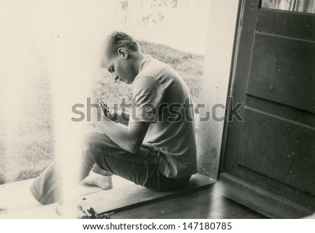 Vintage photo of man sitting on doorstep, forties  - stock photo