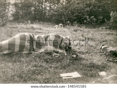 Vintage photo of man sleeping outdoor, eighties - stock photo