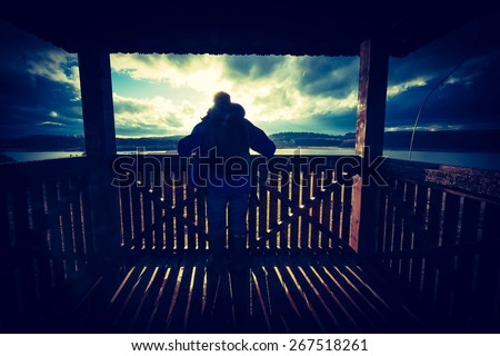 Vintage photo of man standing on observation point (high observation tower). Tourist or birdwatcher  looking on lake from wooden watchtower with roof. - stock photo