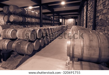 Vintage photo of many wooden barrels in wine cellar - stock photo