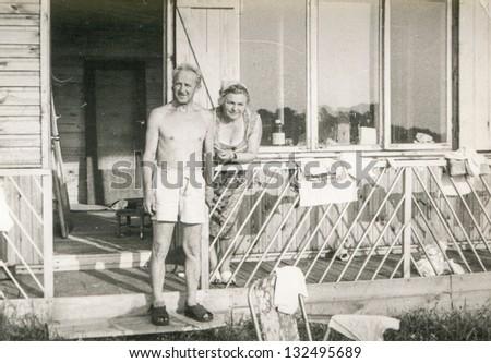 Vintage photo of mature couple on balcony (seventies) - stock photo