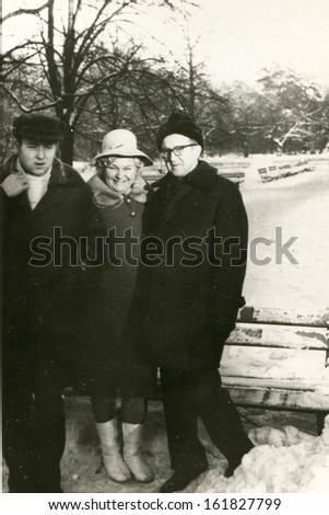 Vintage photo of mature parents with adult son in winter, sixties - stock photo