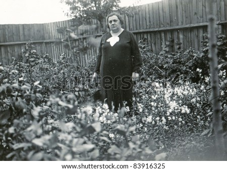 Vintage photo of mature woman in the garden (forties) - stock photo