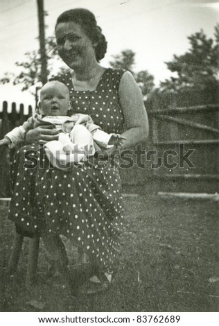Vintage photo of mother and baby daughter (fifties) - stock photo