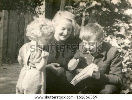 Vintage photo of mother and children reading a book outdoor, fifties - stock photo