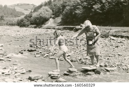 Vintage photo of mother and daughter crossing a river, sixties - stock photo