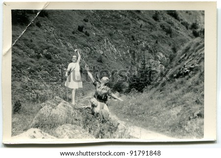 Vintage photo of mother and daughter in mountains (sixties) - stock photo