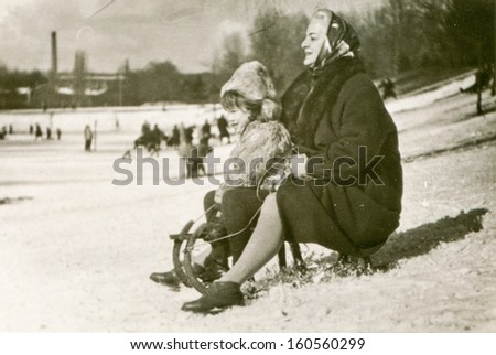 Vintage photo of mother and daughter in winter, sixties - stock photo