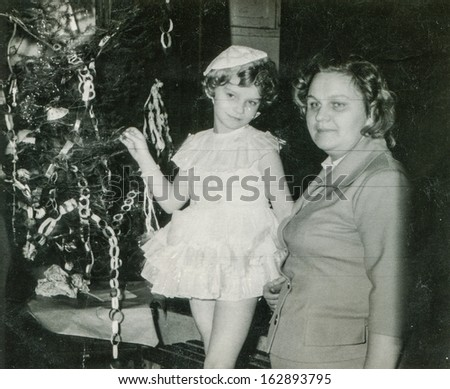 Vintage photo of mother and daughter near Christmas tree, fifties - stock photo