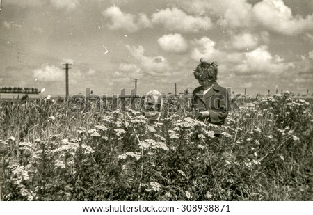 Vintage photo of mother and daughter on blooming meadow, 1950's - stock photo
