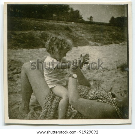 Vintage photo of mother and daughter playing outdoor (fifties) - stock photo