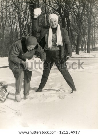 Vintage photo of mother and daughter playing with snowballs (sixties) - stock photo